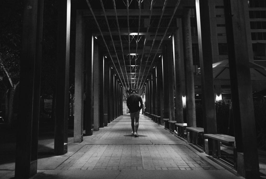 Long dark walkway with side pillars with man walking away.
