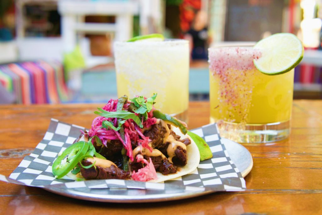 Bright and colourful plate of a taco and a yellow cocktail.
