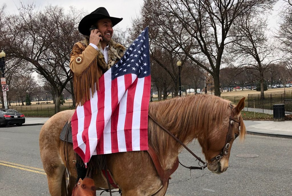 Cowboy on a horse with an American flag on the street