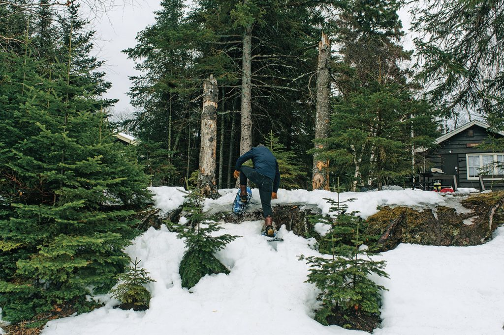 Man climbing a snowy rock in the forest