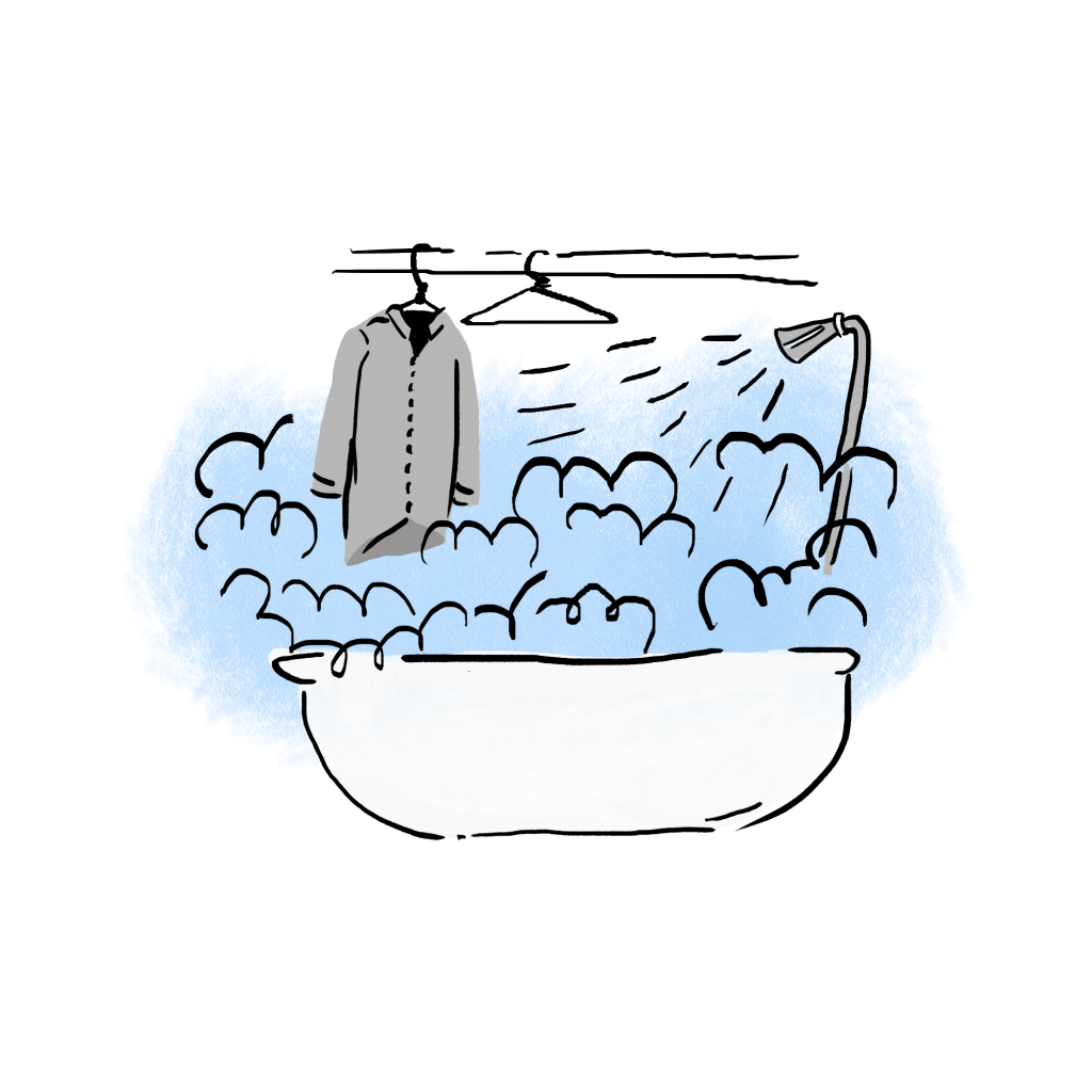 Bathtub with a hot shower steaming a hanging shirt.