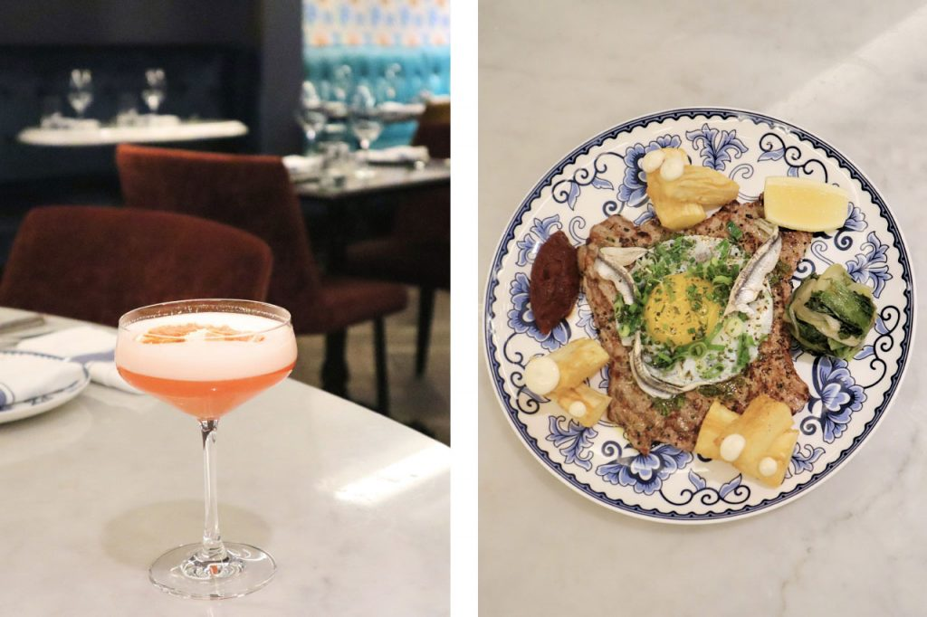 A martini glass pink cocktail, and a plate of meat with an egg yolk on top.