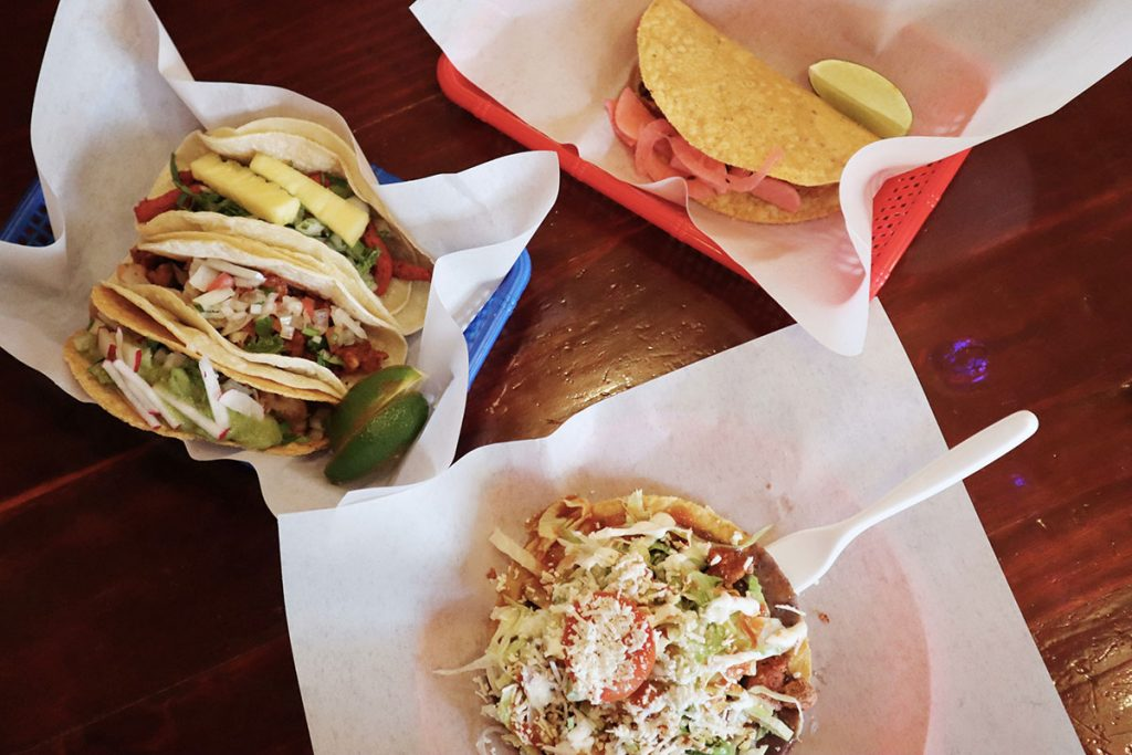 A plastic basket of tacos, and flatbread topped with cheese, meat and tomato.